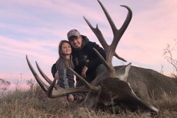 Young girl and dad after shooting her first deer hunting