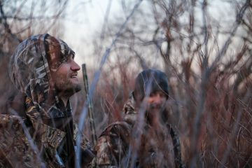 Two men in hunting camo sitting in the woods